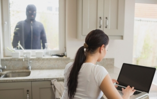 burglar looking in window at woman on computer