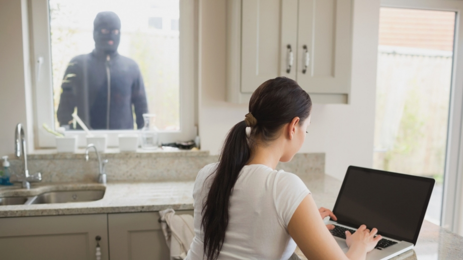 burglar looking in window at woman on computer