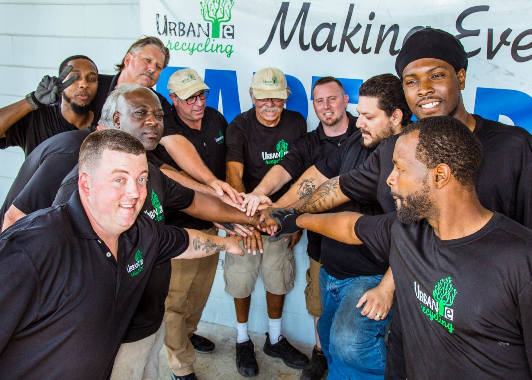 Urban E Team with hands in a huddle
